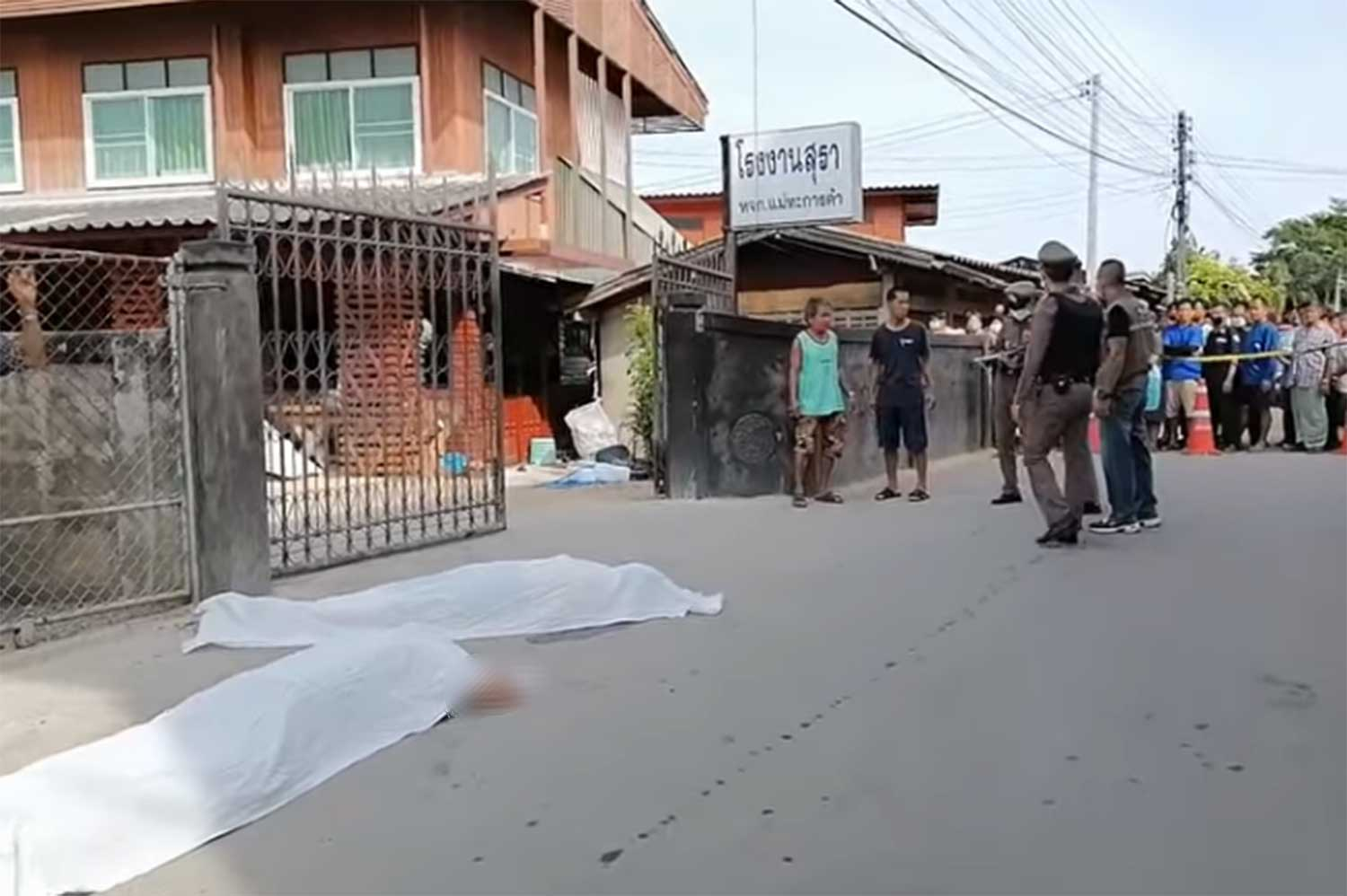 Police inspect the crime scene in front of a house in Mae Tha district, Lampang, where a 52-year-old man shot dead two male relatives and a stabbed a woman on Friday morning. Sheets cover the bodies of the two slain men. (Capture: video on YouTube by Hot News Lampang)