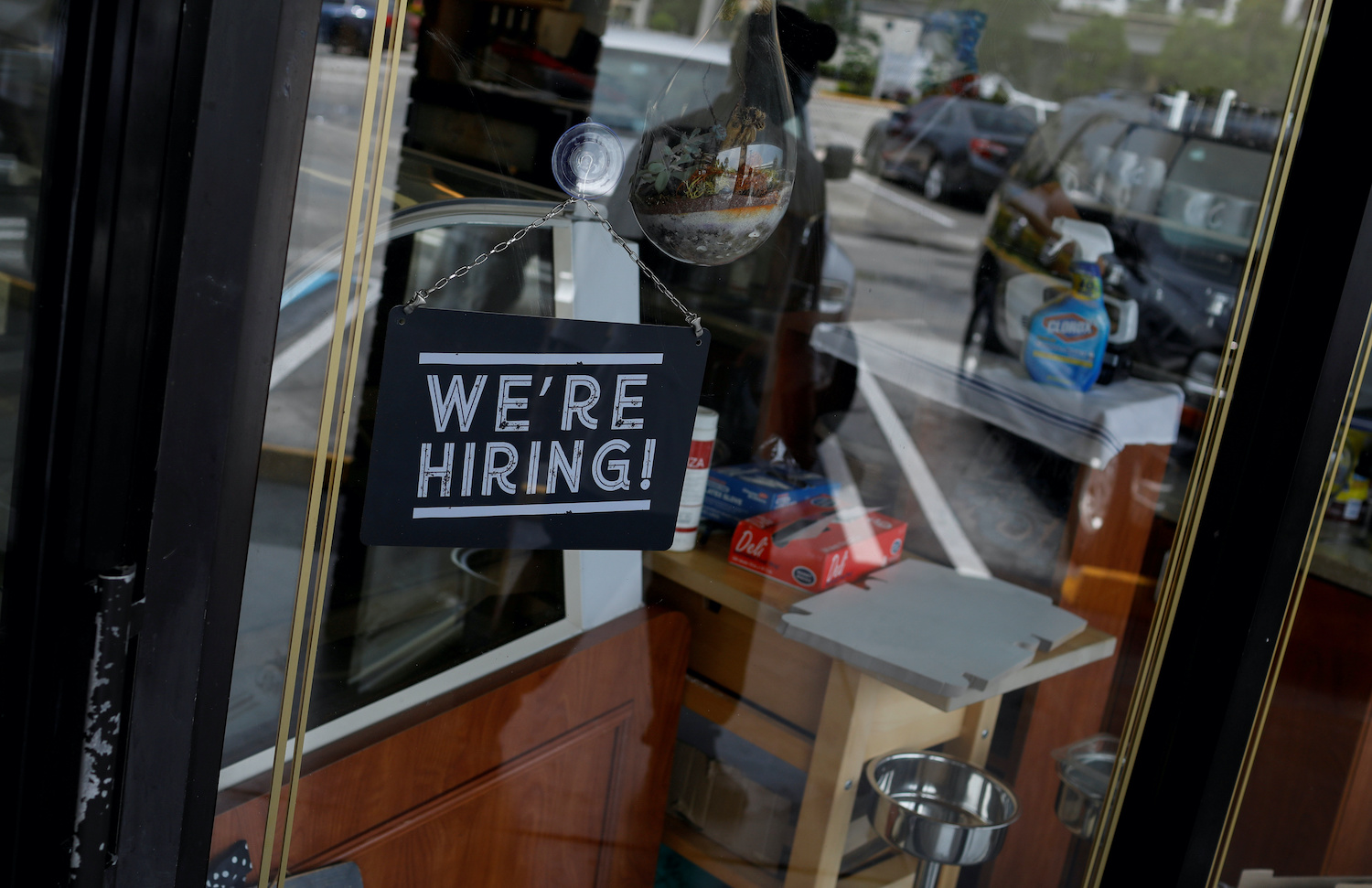 """A """"We're Hiring"""" sign is seen at the entrance of a restaurant in Miami in May. (Reuters Photo)"""