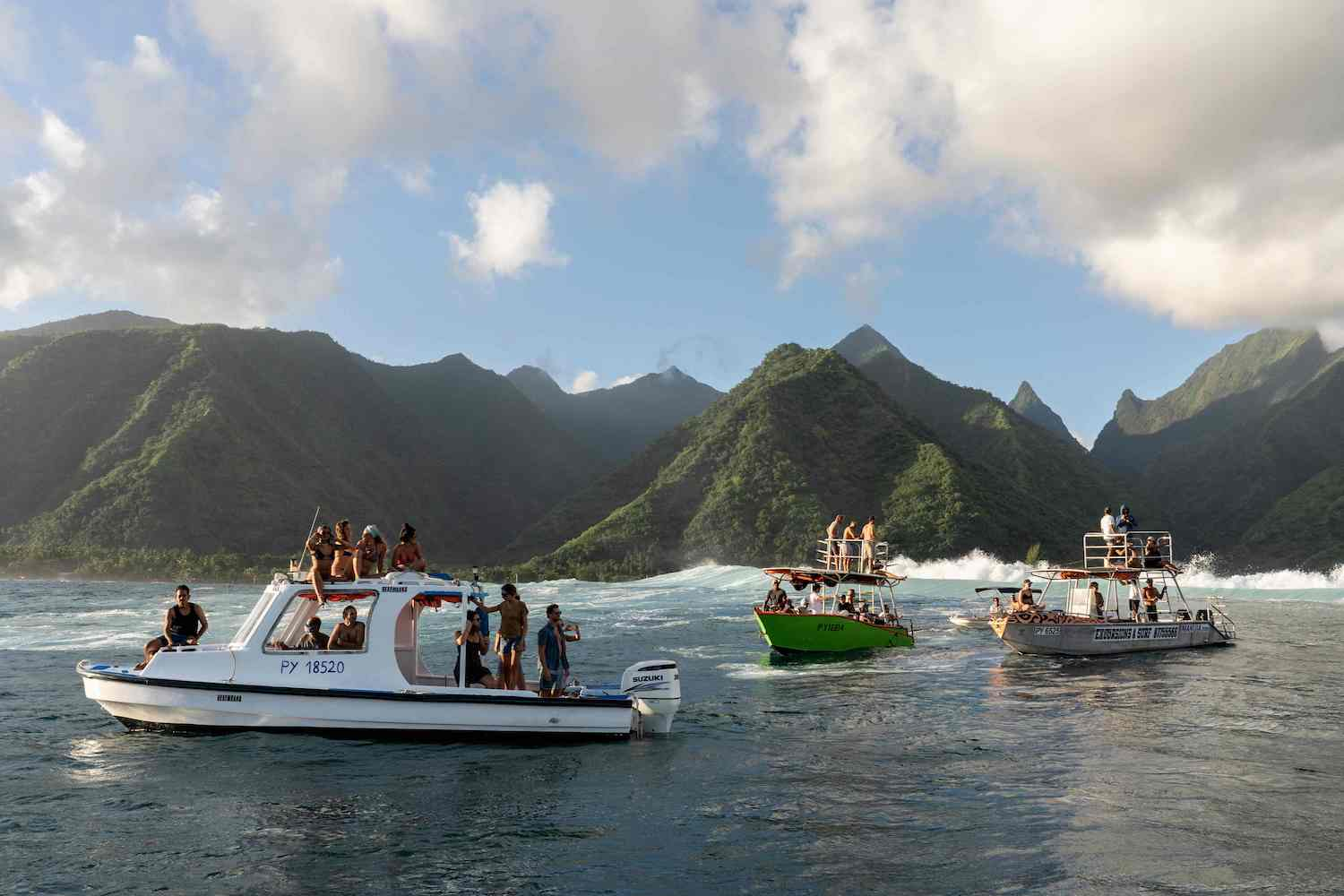 """Spectators gather on """"taxi boats"""" as they prepare to watch local surfers in action at Teahupoo off the coast of Tahiti in French Polynesia on May 11. Teahupoo has been chosen to host the surfing events of the Paris 2024 Olympic Games. (AFP Photo)"""