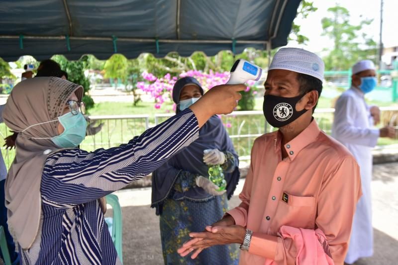 A public health officer checks the temperature of a man as he arrives to attend Friday prayers at a mosque in the southern province of Narathiwat on Friday, as restrictions aimed at curbing the spread of the Covid-19 novel coronavirus are slowly eased. (AFP photo)