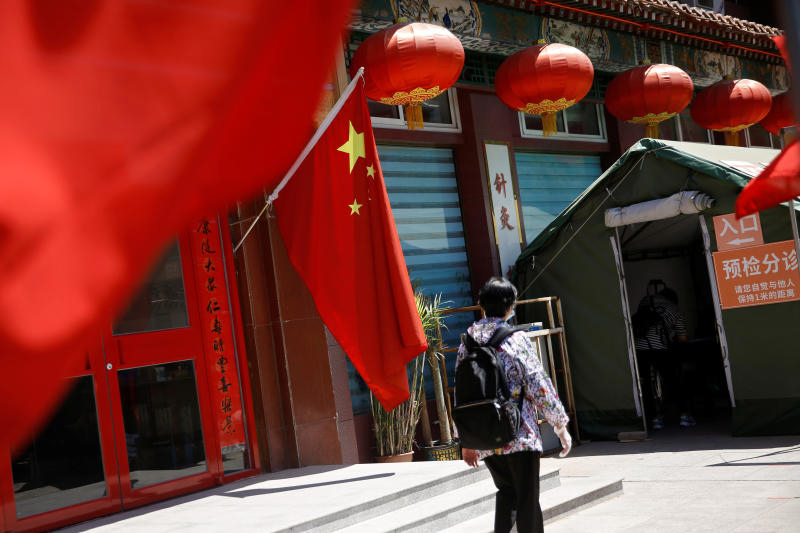 A woman walks outside a traditional Chinese medicine hospital decorated with a Chinese flag in Beijing on May 19, 2020 following the coronavirus disease outbreak. (Reuters photo)