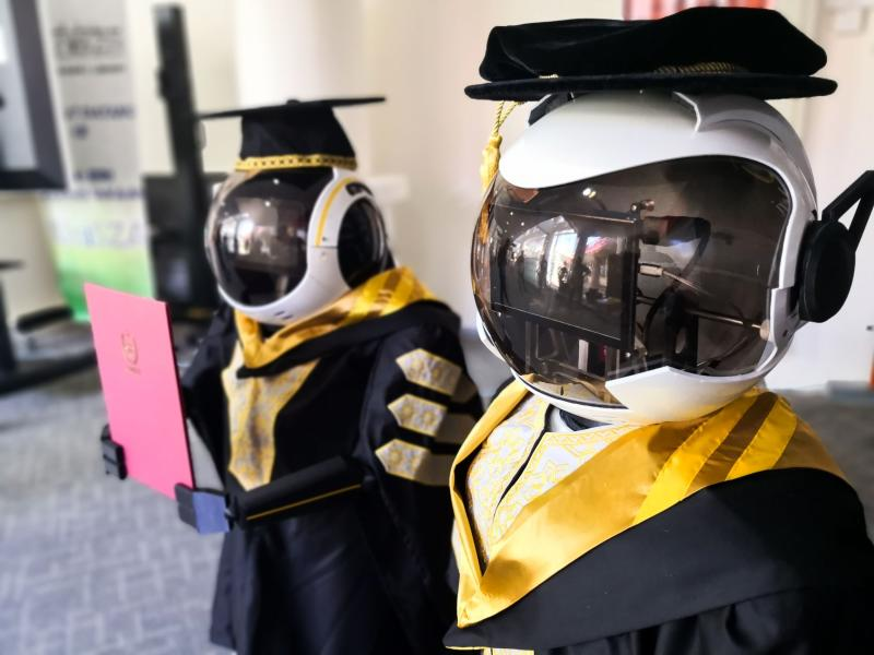 This undated handout photo released by the University Sultan Zainal Abidin on June 2, 2020 shows two robots wearing graduation robes during a simulation in Terengganu. A Malaysian university in the eastern state is looking at robots to stand in for graduating students amid fears over the spread of the coronavirus. (Photo by Handout / UNIVERSITY SULTAN ZAINAL ABIDIN / AFP)