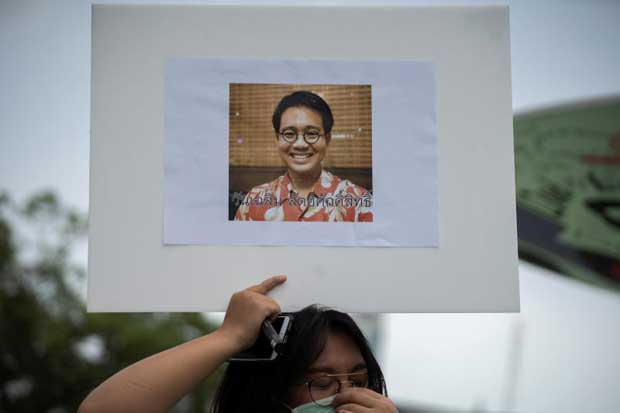 An activist holds a picture of Wanchalearm Satsaksit during a protest for his disappearance in Bangkok on Friday. (Reuters photo)