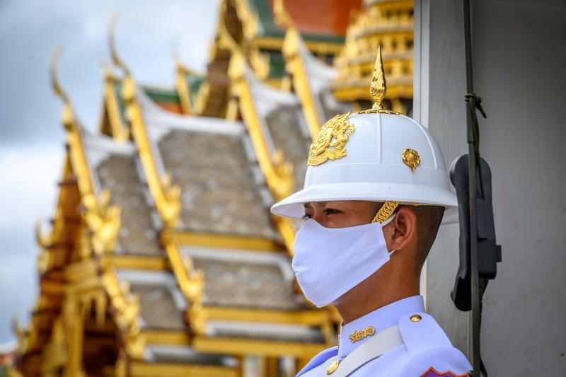 A soldier stands guard in front of the Grand Palace in Bangkok on Sunday, as it reopened for visitors following restrictions to halt the spread of the Covid-19 novel coronavirus. (AFP photo)