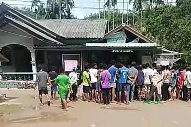 Neighbours gather in front of a store after Sudrak Noodaeng was shot dead in Bang Khan district of Nakhon Si Thammarat province on Sunday. Shop owner Thamthep Rodkong told police the man charged at him with a knife and he fired his gun in self-defence. (Photo:  Nujaree Raekrun)