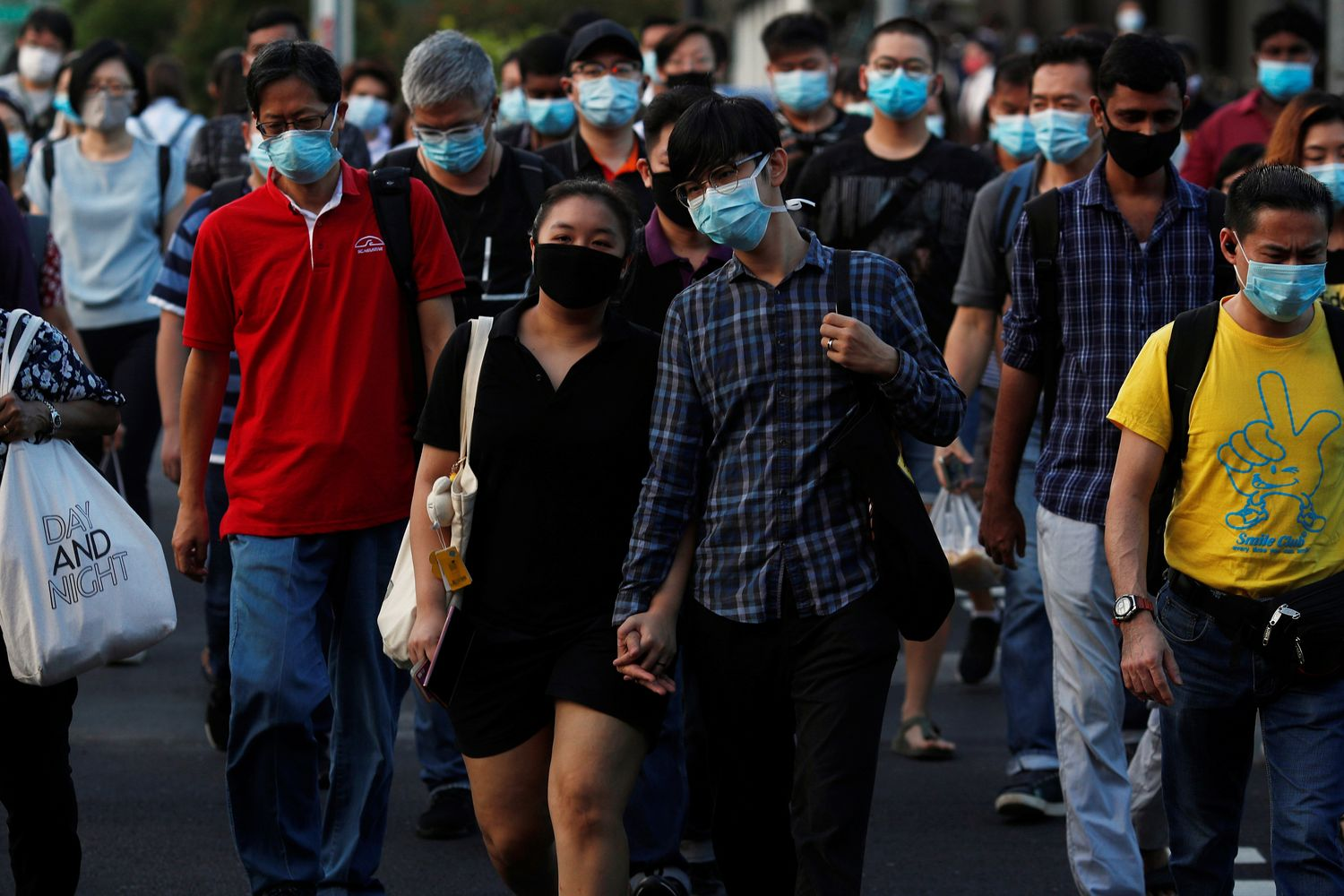 People cross a street during morning peak hour commute amid the coronavirus disease outbreak in Singapore on Wednesday. (Reuters photo)