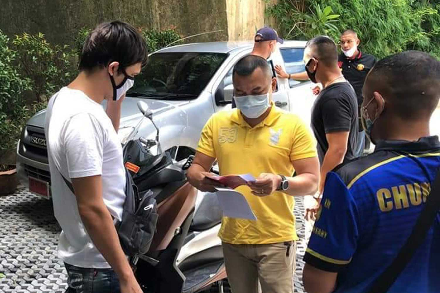 Leonid Iuraovskii, 35, white T-shirt, is arrested in Patong, Phuket, on Wednesday on charges of embezzlement and falsifying documents in the fraudulent sale of tour packages to his compatriots. (Photo supplied)