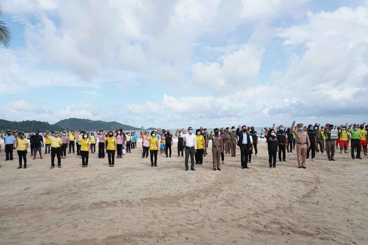 Phuket officials raise their hands as the island province's beaches are reopened for public use, at Patong beach on Tuesday. (Photo: Achadtaya Chuenniran)