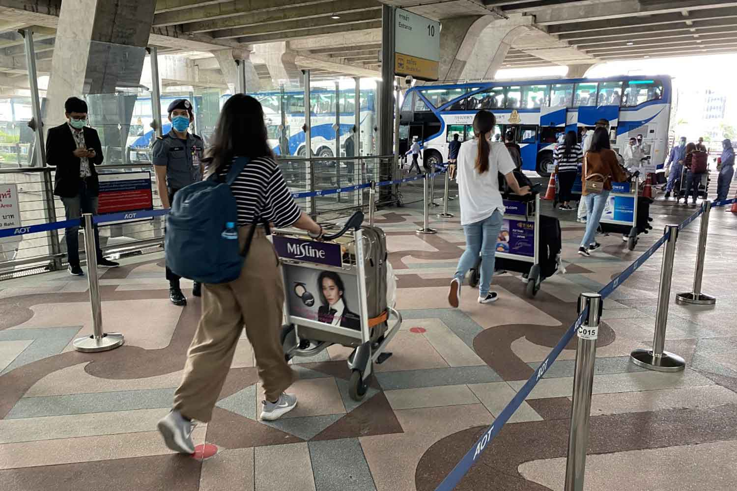 Returnees board buses at Suvarnabhumi airport, heading for 14-day quarantine, after arriving home from Japan on Tuesday. (Photo: Sutthiwit Chayutworakan)