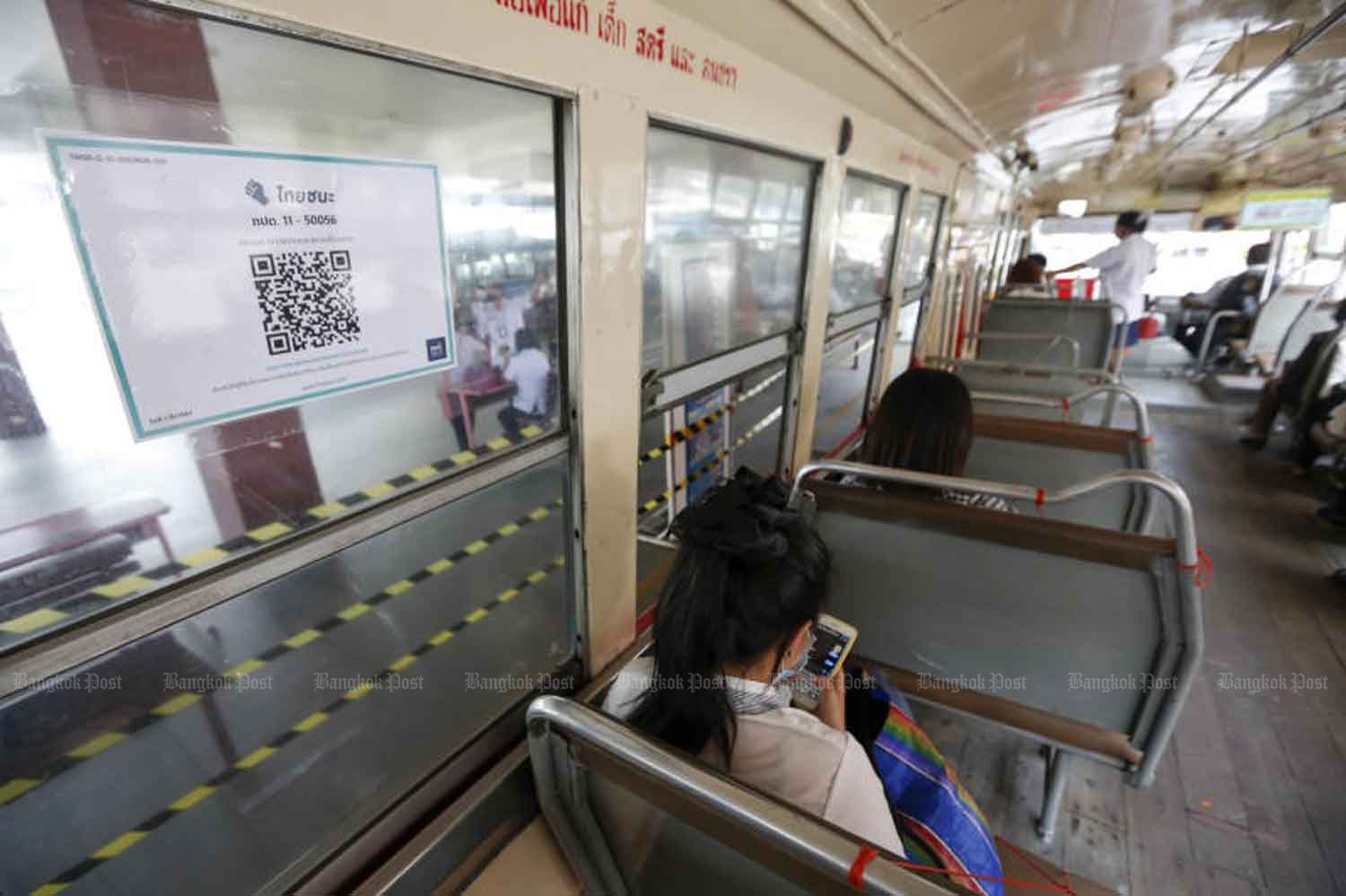 A QR code on the window of a Bangkok bus, for commuters to check in and check out to help control Covid-19. (Photo: Pattarapong Chatpattarasill)