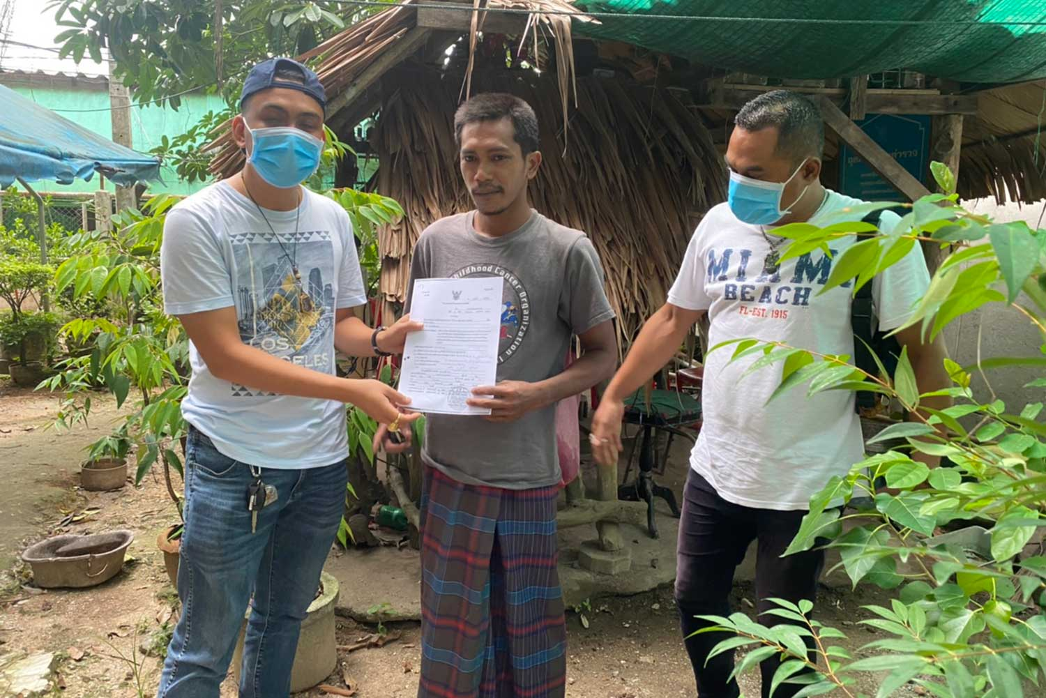 Plainclothes police shows an arrest warrant to Maleekee Jarong, accused of allegedly raping a woman in Samut Prakan and posting her nude photos online, when arresting him at his house in Yarang district, Pattani, on Thursday morning. (Supplied photo)
