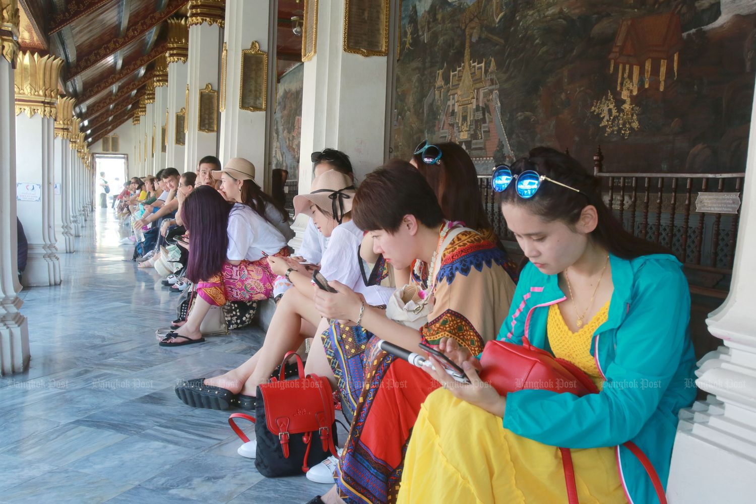 Chinese tourists rest during a visit to the Grand Palace in Bangkok in 2018. (Bangkok Post file photo)