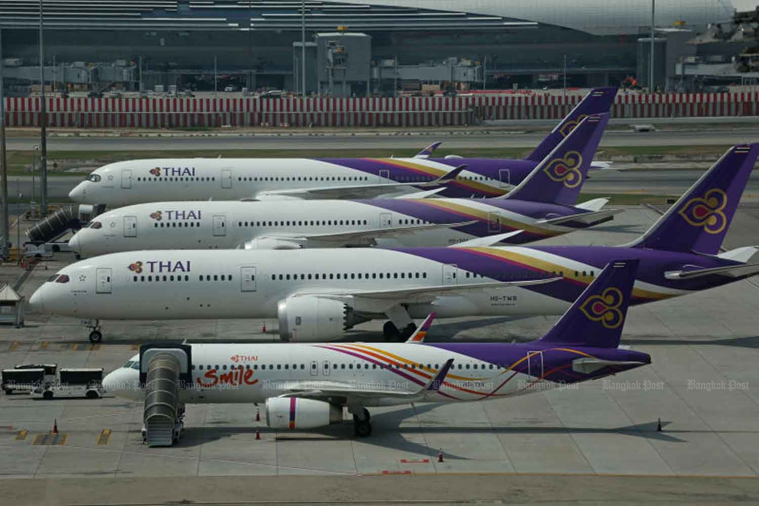 Thai Airways International and THAI Smile planes are grounded on the tarmac at Suvarnabhumi airport. (Bangkok Post photo)
