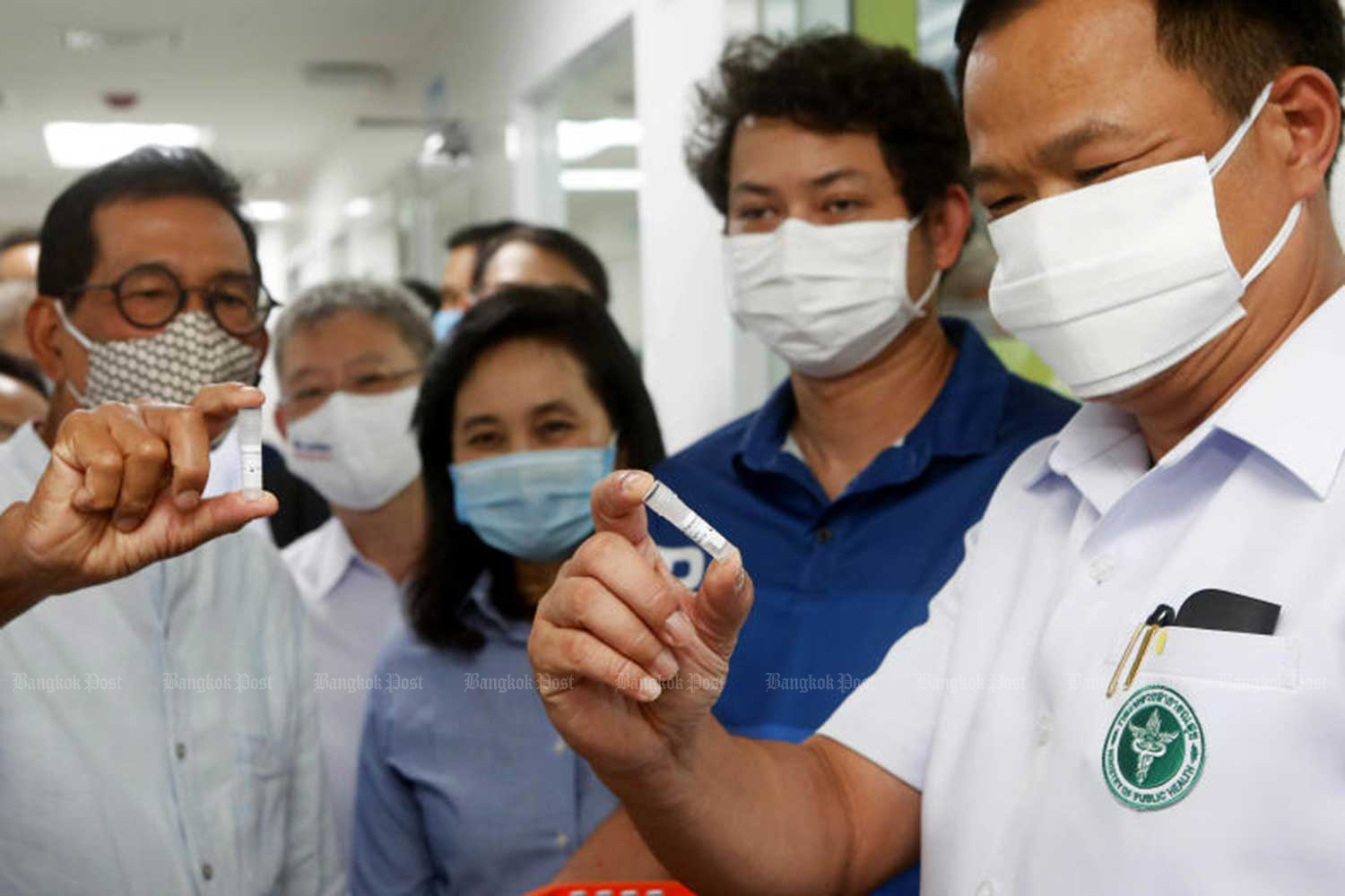 Pulic Health Minister Anutin Charnvirakul, right, looks at solution samples at the Siam Bioscience Group, which produces Covid-19 test kits, on June 1. (Photo: Pattarapong Chatpattarasill)