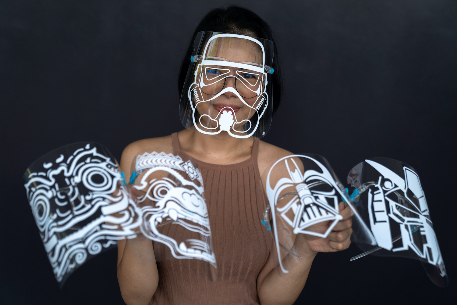 Maysa Talerd models a Star Wars stormtrooper face shield and shows other versions that draw on everything from cartoons to Khon. (Reuters Photo)