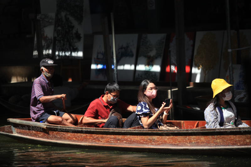 Visitors take a tour at the busy Damnoen Saduak floating market in Ratchaburi on May 31. (Photo by Arnun Chonmahatrakool)