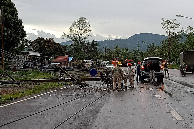 Workers inspect electricity poles toppled by a storm in Muang district of Phayao on Saturday. (Photo by Saiarun Pinaduang)