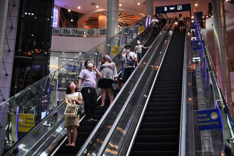 People ride an escalator with social distancing signs, aimed at preventing the spread of the Covid-19 novel coronavirus, at the Terminal 21 shopping mall in Bangkok on Monday. (AFP photo)