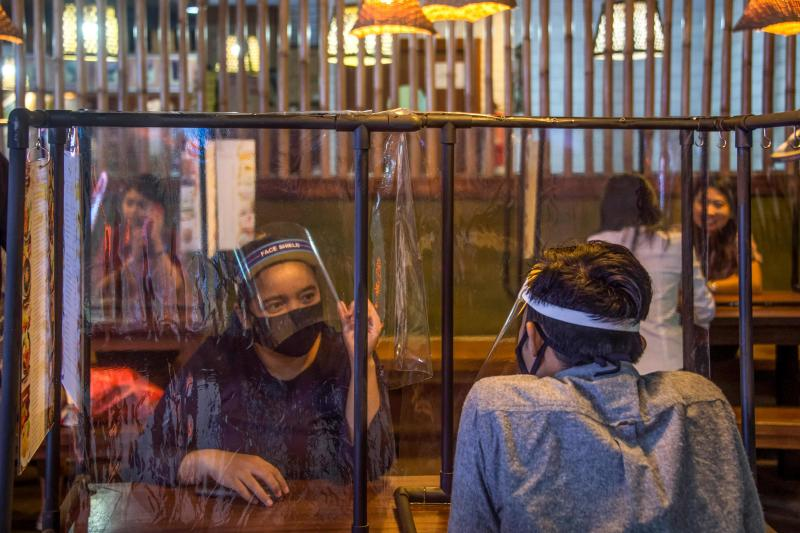 Young people sit in a restaurant with plastic dividers to apply social distancing rules amid concerns for the COVID-19 coronavirus at a shopping mall in Surabaya, East Java on Tuesday (AFP)