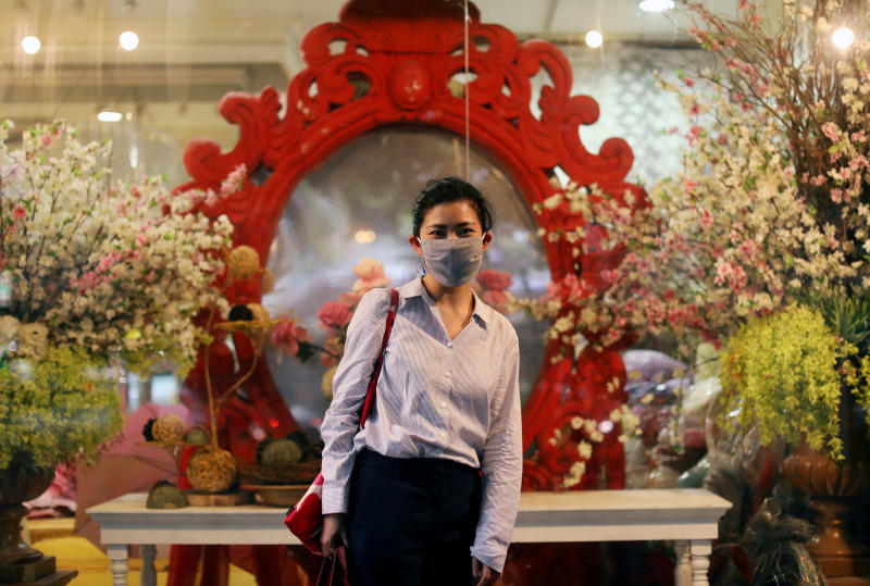 A woman wearing a protective mask poses in front of a flower shop, after the government eased some protective measures following the coronavirus disease (Covid-19) outbreak in Bangkok on Wednesday. (Reuters photo)