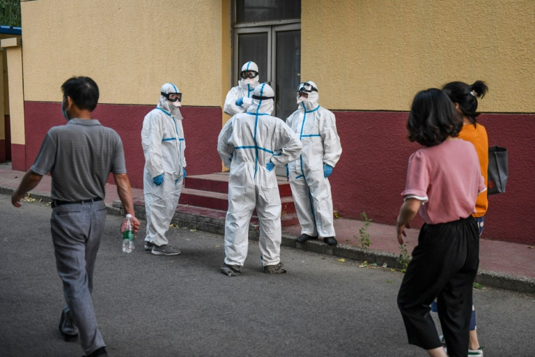 Medical workers in protective equipment take a break at a testing centre for COVID-19 in Beijing this week after a new outbreak whch is also casting fresh doubts over the suspended Chinese Super League football season