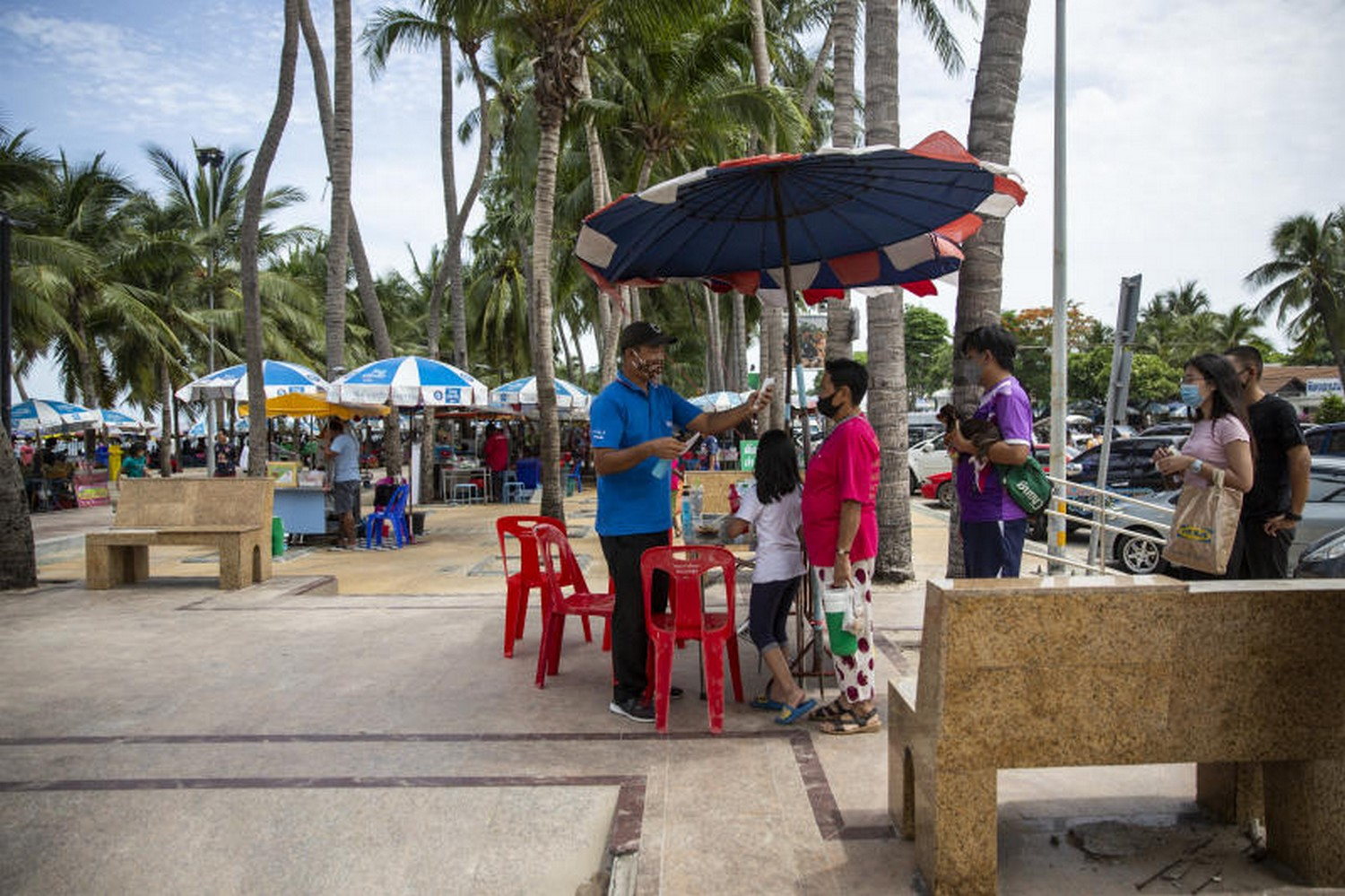 Back to the beaches: A visitor wearing a protective mask has her temperature checked at an entrance screening point at Bangsaen beach in Chonburi last Sunday. (Photo: Bloomberg)
