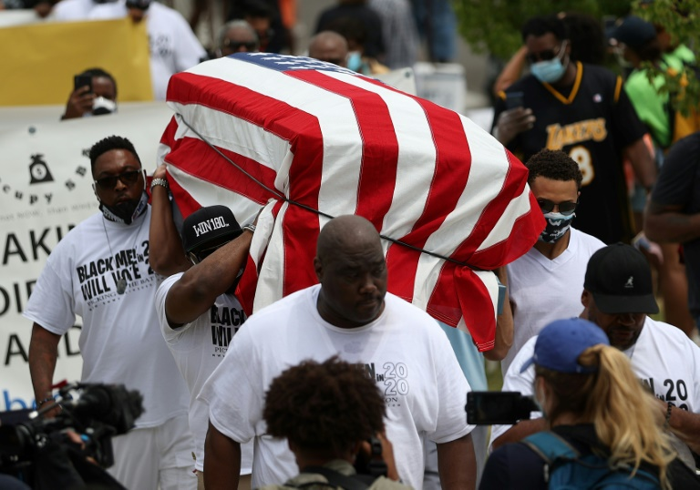 Protesters carry an empty symbolic casket draped with an American flag during a Juneteenth march in Tulsa, Oklahoma
