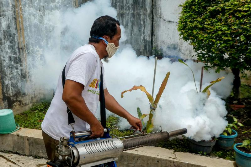 A man fumigates an area as part of community measures to control a dengue outbreak at a housing complex in Jakarta on April 11, 2020. (AFP photo)