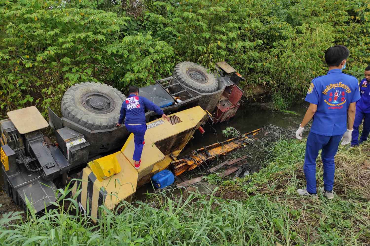 Rescuers try unsuccessfully to help the trapped driver of the partially submerged mobile crane, which toppled into this deep ditch when the edge of the road crumbled, in Tha Muang district, Kanchanaburi on Monday. (Photo: Piyarat Chongcharoen)