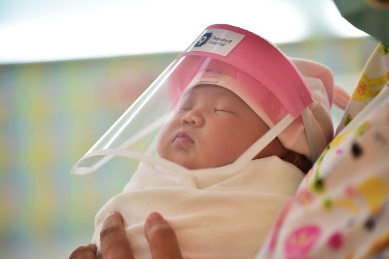 This file photo taken on April 9, 2020 through a glass window at a maternity ward shows a newborn baby wearing a face shield, in an effort to halt the spread of the Covid-19 coronavirus, at Praram 9 Hospital in Bangkok. (AFP)