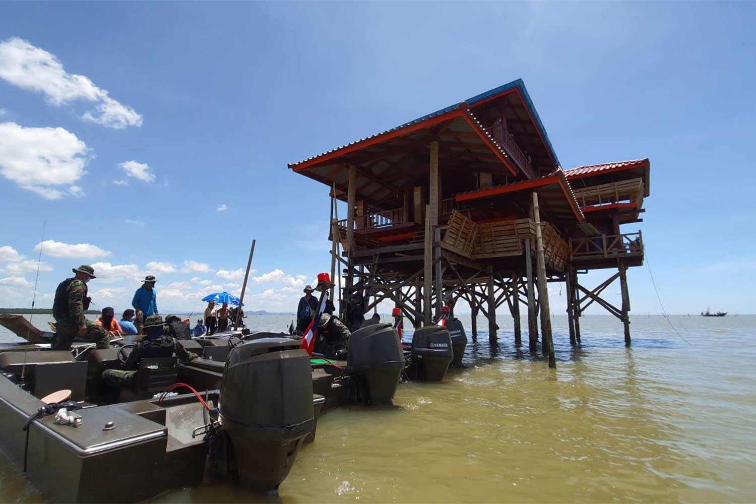 Officials arrive to supervise dismantling of a roofed platform built to guard a cockle farm in Bandon Bay of Surat Thani. (Photo: Supapong Chaolan)