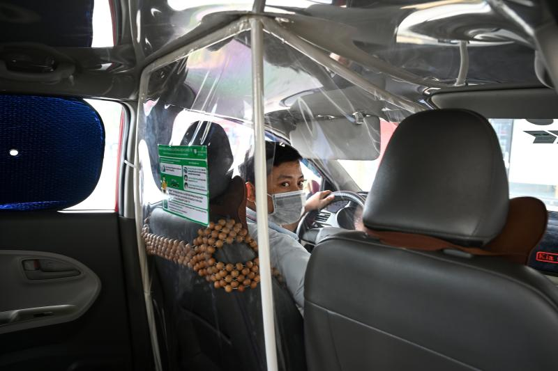 In this file photo taken on May 19, 2020 a taxi driver wearing a face mask looks on from behind a plastic screen as a preventive measure against the spread of Covid-19 novel coronavirus, in Hanoi. (AFP)