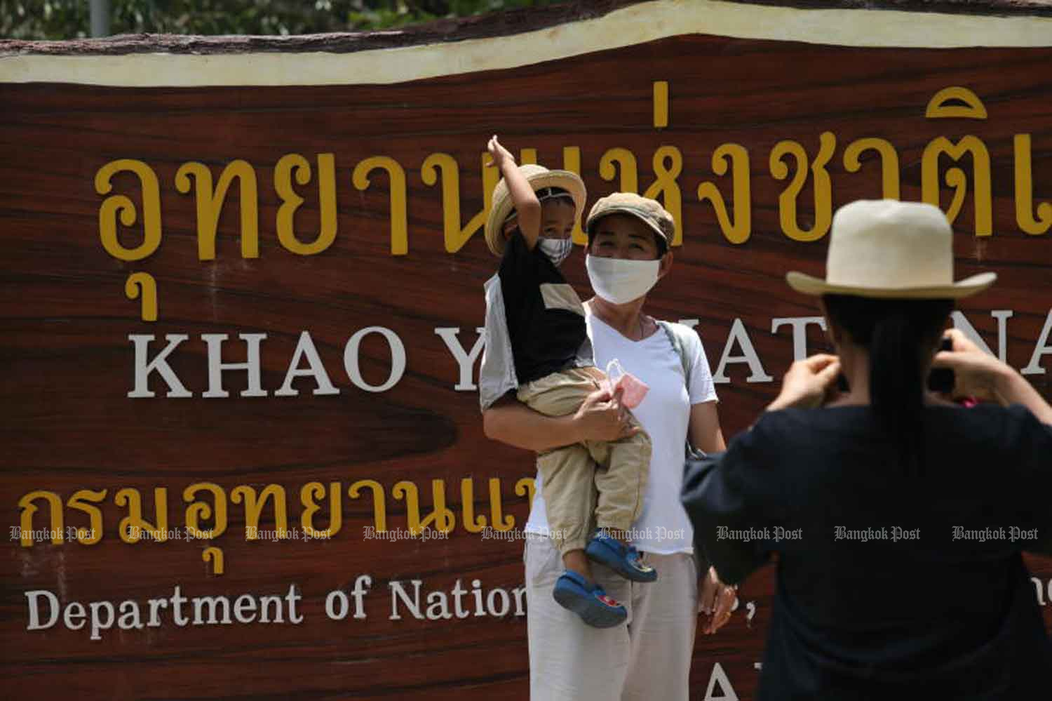 Visitors pose for photos at the entrance of Khao Yai National Park in Nakhon Ratchasima province on Thursday, when four new Covid-19 cases were detected. (Photo: Arnun Chonmahatrakool)