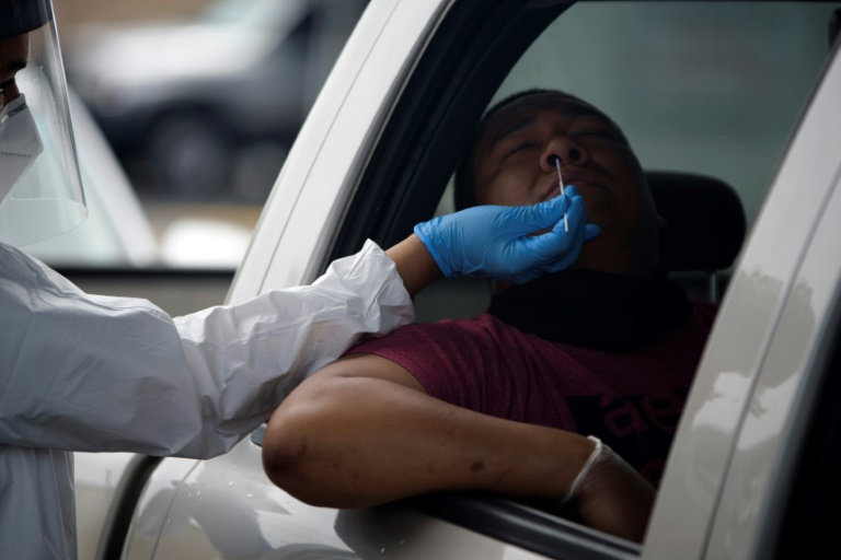 A healthcare worker administers a COVID-19 test at the United Memorial Medical Center testing site in Houston, Texas on June 25