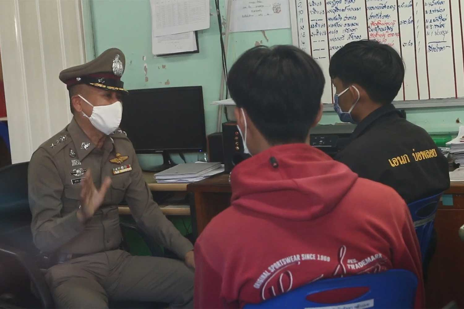 An officer at the Tha Muang police station in Kanchanaburi interrogates two young men on Saturday about the mysterious death of a schoolgirl on June 17. (Photo: Piyarach Chongcharoen)