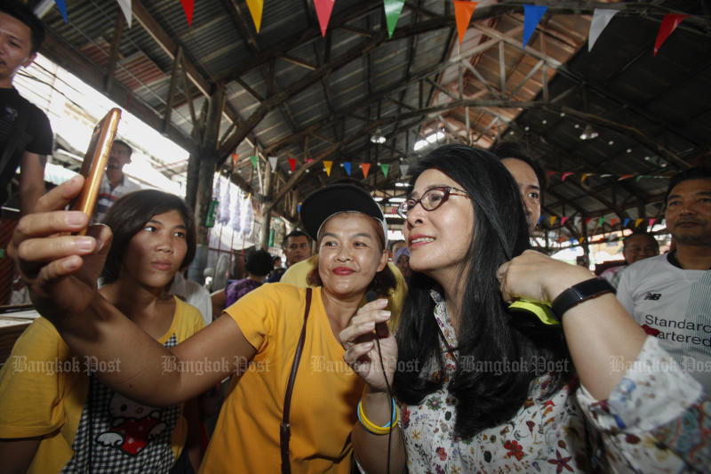 Pheu Thai chief strategist Khunying Sudarat Keyuraphan takes a selfie with supporters during a campaign in Bangkok Noi district, Bangkok, on Aug 17, 2019. The party is still the first choice for northeastern voters in a Khon Kaen University poll released on Sunday. (Bangkok Post file photo)