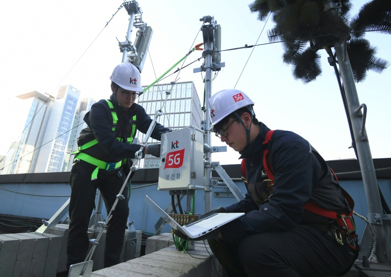 Technicians of South Korean telecom operator KT check an antenna for the 5G mobile network service in Seoul.