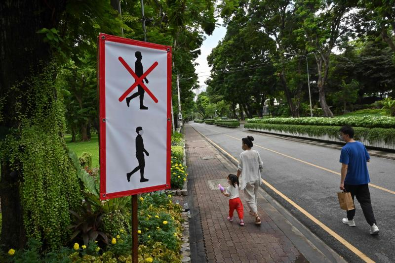 This photo taken on Sunday shows a couple with a child walking past a sign advising visitors to wear face masks at Lumpini Park in Bangkok to prevent the spread of the Covid-19 novel coronavirus. (AFP)