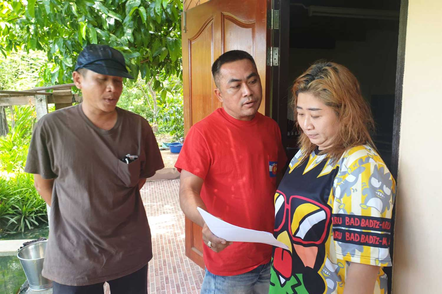 Plainclothes police serve an arrest warrant on the 40-year-old woman accused of procuring young girls for the flesh trade in Ratchaburi, in Amphawa district of Samut Songkram province on Monday. (Photo supplied)
