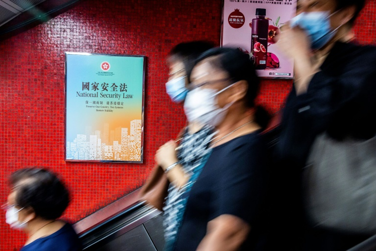 A government advertisement (left) promoting China's national security law is displayed inside an MTR train station in Hong Kong.