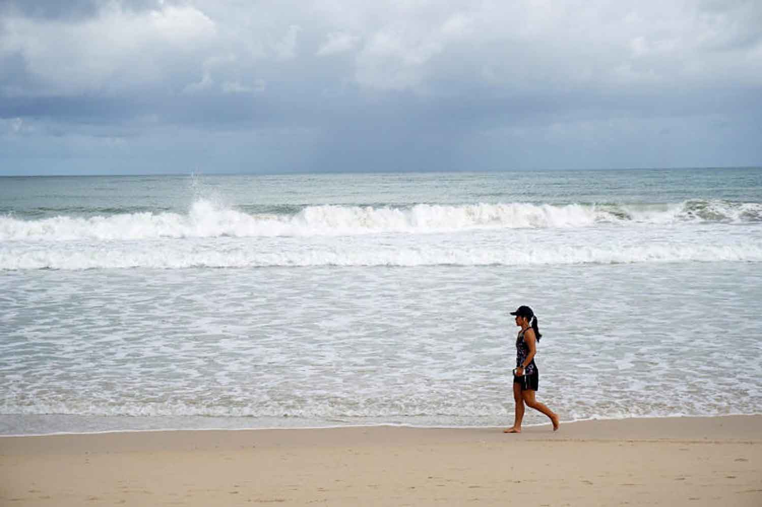 A tourist walks on the beach of Phuket early last month when the southern island province reopened its beaches to jumpstart its economy after months of lockdown. (Photo: Achadtaya Chuenniran)