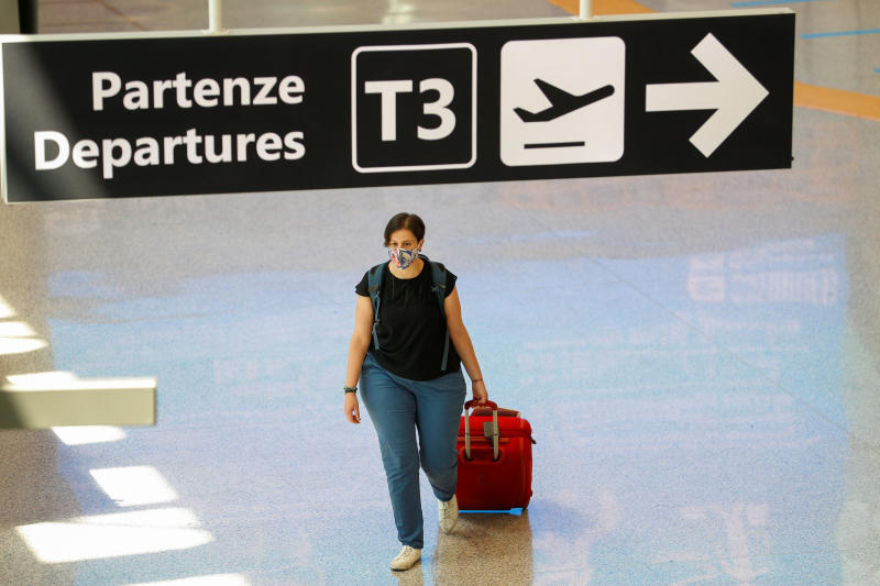 A passenger wearing a protective face mask walks at Fiumicino Airport in Rome on the day EU governments agreed a