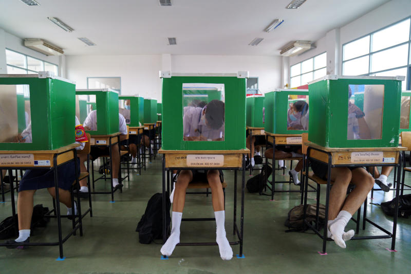 Students from Sam Khok school wearing face masks and face shields are seen inside old ballot boxes repurposed into partitions as they attend a class, after schools nationwide reopened, at Pathum Thani on Wednesday. (Reuters photo)