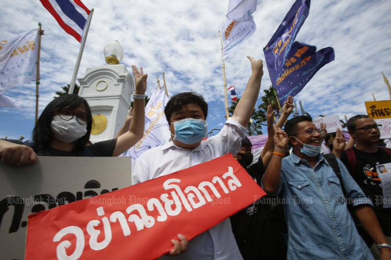 Members of the anti-government People Go Network group carry placards outside Government House on Monday demanding the immediate revocation of the emergency decree imposed to contain the Covid-19 pandemic. (Photo by Pornprom Satrabhaya)