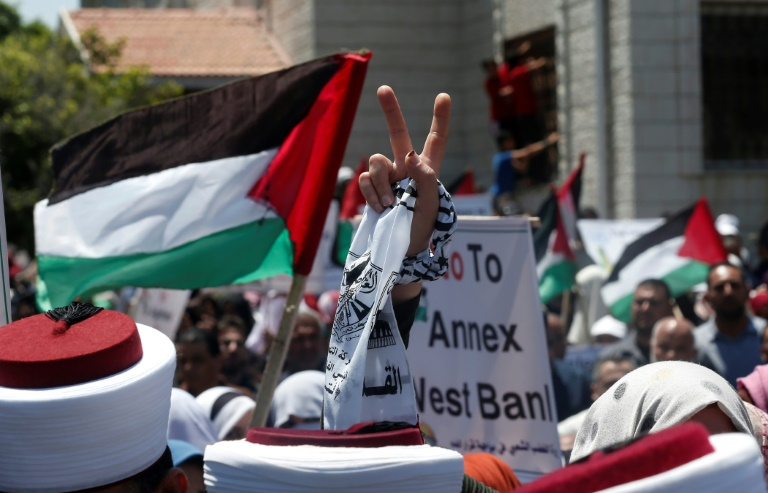 A Palestinian demonstrator in Gaza City flashes the victory sign in