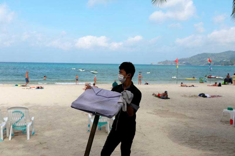 A waiter works in a beach with a few Western tourists, which is usually full of Chinese tourists, amid fear of coronavirus in Phuket on March 10, 2020. (Reuters photo)