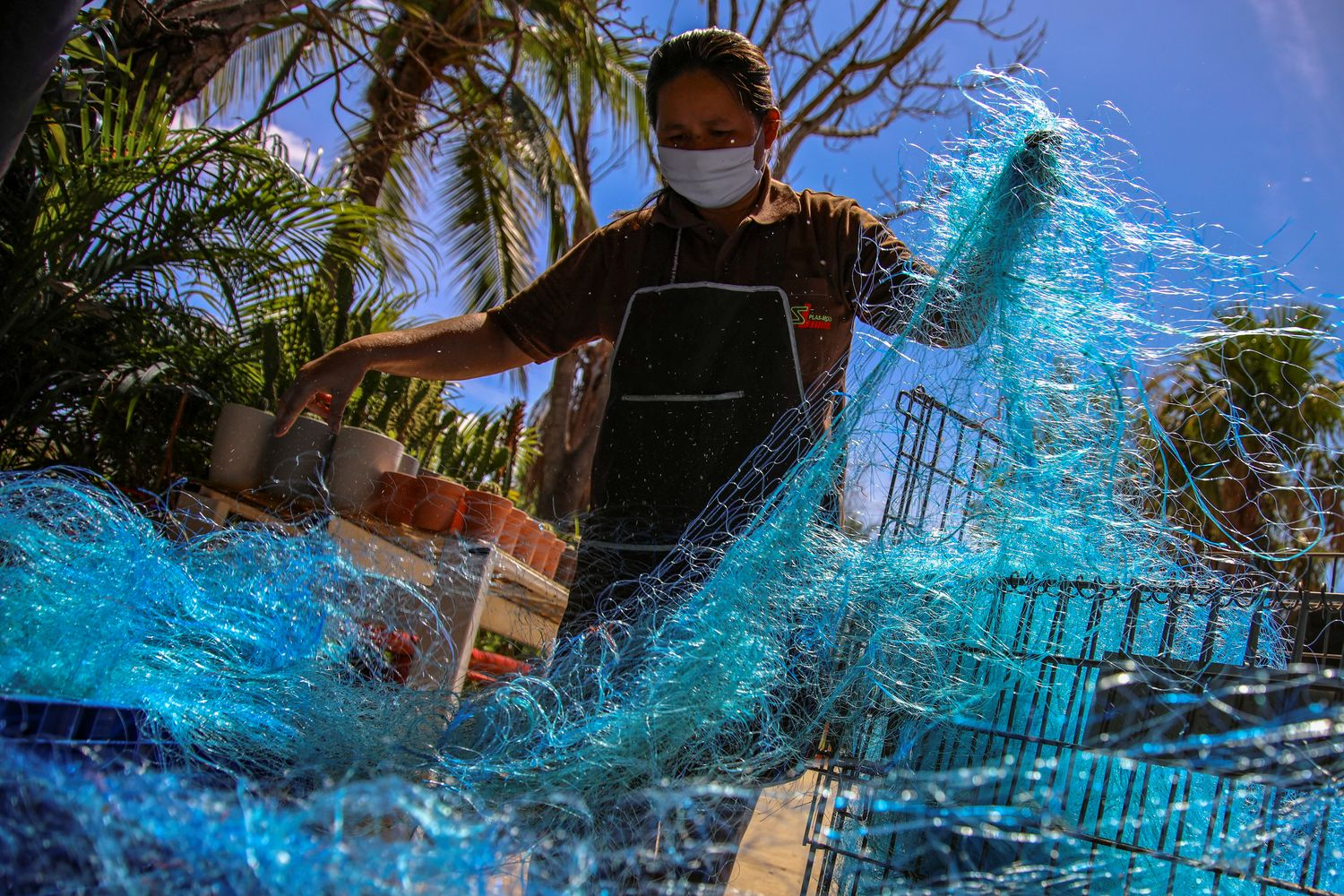 A worker prepares old fishing nets before a recycling process to create, among new products, protective gear against the coronavirus disease at the Saint Louis Plas Mold factory amid the COVID-19 outbreak in Ayutthaya province on Tuesday. (Reuters photo)