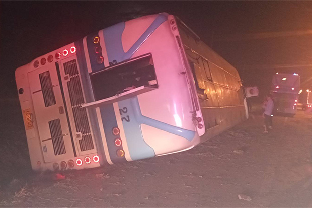 The overturned Charn Tour bus blocks the main highway in Sung Noen district of Nakhon Ratchasima early on Friday. (Photo: Prasit Tangprasert)