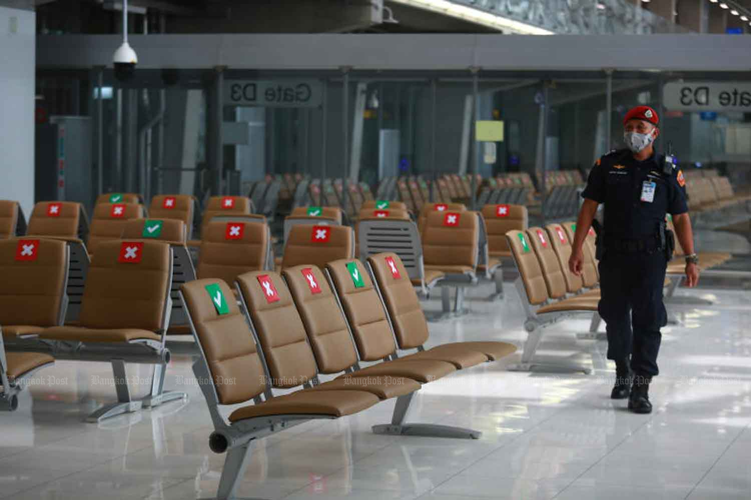 A security guard checks the passenger terminal at Suvarnabhumi airport in Samut Prakan province on Friday. The first foreign visitors since the coronavoirus lockdown started will be arriving this month - selected groups, for specific purposes. (Photo: Somchai Poomlard)