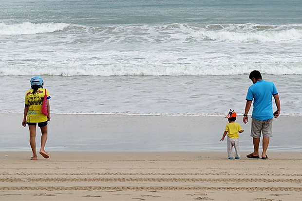 A family enjoys a walk at a beach on Koh Phuket in June. The island is slowly opening up for the return of foreign tourists. (Photo: Achadtaya Chuenniran)